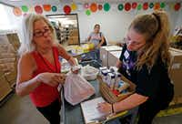 Volunteers Ellen Brude (left) and Grace Dickerson, 15, gather up groceries for client Lorena Baires at Crossroads Community Services. (Jae S. Lee/Staff Photographer)