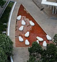 Jan Mak, a senior project architect at UNT, submitted a Curious Texas question about the stones in the Main Street Garden Park fountain. The stones, he says, look like coffins. The art is photographed in downtown from atop the Statler Hotel in Dallas.(Louis DeLuca/Staff Photographer)