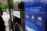 A customer opens the door of a Washington state Dept. of Licensing office in Lacey, Wash., Friday, June 22, 2018 next to a sign providing information about the requirements of Real ID.(Ted S. Warren/The Associated Press )