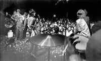 Rolling Stones Keith Richards (left) and Mick Jagger (right) sing on the rose petal-littered stage during the  concert at Altamont Speedway on  Dec. 6, 1969. Hells Angels (far left) held back the surging crowd. The hand of drummer Charlie Watts is shown in foreground.  (Anonymous/The Associated Press)