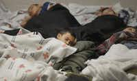 Migrant children slept in a holding cell at a U.S. Customs and Border Protection processing facility in Brownsville in 2014.(Eric Gay/The Associated Press)