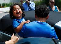 Ever Reyes Mejia, of Honduras, carries his son to a vehicle after being reunited and released by United States Immigration and Customs Enforcement in Grand Rapids, Mich., Tuesday, July 10, 2018. Two boys and a girl who had been in temporary foster care in Grand Rapids were reunited with their Honduran fathers after they were separated at the U.S.-Mexico border about three months ago.(Paul Sancya/The Associated Press)