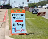 Signs along Garland Road point the way to the White Rock Lake Farmers Market.(Ron Baselice/Staff Photographer)