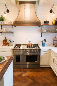 There's no denying the Parisian influence with a custom copper vent hood over a professional gas range, says Tara Lenney.(Tara Lenney Design)