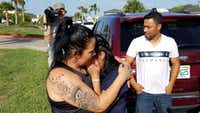 Reina, 40, of El Salvador, with family friend Carlo Mauricio Rodriguez, hugs her 17-year-old daughter Diana after they were reunited on July 13 at a federally contracted shelter in south Texas.(TNS/Molly Hennessy-Fiske)