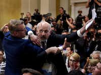 Security removes an apparent protester before a joint press conference between U.S. President Donald Trump and Russia President Vladimir Putin in the Presidential Palace in Helsinki, Finland.(Antti Aimo-Koivisto/AP)