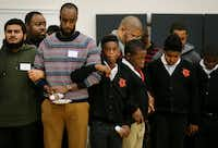 "Students and mentors lock arms during a prayer at the end of the ""Breakfast with Dads"" event at Billy Earl Dade Middle School in Dallas on Dec. 14, 2017. (Andy Jacobsohn/Staff Photographer)"