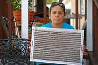 Rosa Ayala shows a caked up air filter recently swapped out at her home in McKinney's High Point Mobile Home Community. The grime collected on the filter in only two months. (Jae S. Lee/Staff Photographer)