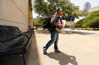 """<p><span style=""""font-size: 1em; background-color: transparent;"""">With her cup of water and peanut butter crackers in one hand and her belongings on her back, Tara Jackson of South Dallas leaves the disappearing shade near the Kay Bailey Hutchison Convention Center for the comforts of the Central Library in downtown Dallas on July 18.</span></p>(Tom Fox/Staff Photographer)"""