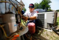 Berkey's technician Brandon Cronkhite adds R-410A refrigerant to an outdoor condensing unit at a Southlake, Texas home, Friday, July 20 2018. The system had a leak and the homeowner asked to recharge it. (Tom Fox/The Dallas Morning News)(Tom Fox/Staff Photographer)