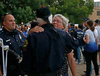 "Delores Givens, mother of Senior Cpl. Earl ""Jamie"" Givens got a hug from retired Dallas police detective Don Casey during a candlelight vigil for her son on Monday.(Jae S. Lee/Staff Photographer)"