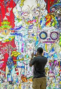 "Dominique Carter takes photos with his cellphone for social media at Takashi Murakami's exhibition, ""The Octopus Eats Its Own Leg,"" at the Modern Art Museum of Fort Worth on July 20, 2018.(Ashley Landis/Staff Photographer)"