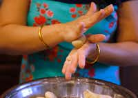 Sapna Punjabi-Gupta rolls out ball of dough prior to cooking roti.(Vernon Bryant/Staff Photographer)
