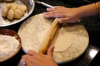 Sapna Punjabi-Gupta rolls out a ball of dough as she prepares to cook roti.(Vernon Bryant/Staff Photographer)