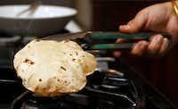 Sapna Punjabi-Gupta finishes off a roti on the open flame to create a puffed phulka.(Vernon Bryant/Staff Photographer)