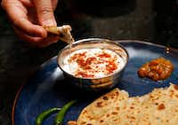 Sapna Punjabi-Gupta dips a paratha in yogurt and spices.(Vernon Bryant/Staff Photographer)
