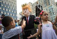 A man dressed to resemble President Donald Trump interacts with children as activists rally against the Trump administration's immigration policies outside the New York City offices of U.S. Immigration and Customs Enforcement on Thursday, July 26, 2018 in New York City. (Drew Angerer/Getty Images)
