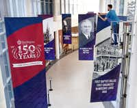 Building technician Micah Lynch hangs banners along an indoor walkway in advance of First Baptist Dallas' 150th anniversary celebration.(Tom Fox/Staff Photographer)