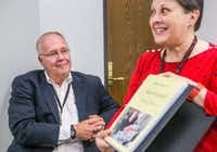 Michael Graczyk, a journalist for The Associated Press, looks at a book of notes written by his colleagues, held by Diana Heidgerd, during a retirement celebration at the AP Dallas News Bureau in Dallas on July 31, 2018. Over his career, Graczyk has witnessed and documented hundreds of executions in Texas. (Carly Geraci/Staff Photographer)