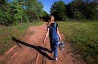 Jeanette Kinman walks down a dirt road to feed the chickens at a spiritual commune called the Adelphi community located  near Terrell about an hour east of Dallas.(Eli Grothe/FILE/The Dallas Morning News)