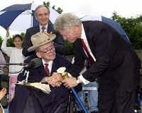 <p>President Clinton accepts the Spirit of ADA torch from human rights advocate Justin Dart during a ceremony at the FDR Memorial in Washington in 2000 to commemorate the 10th anniversary of the Americans with Disabilities Act.</p>