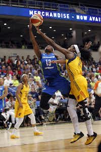 Dallas Wings guard Karima Christmas (13) makes a basket and is fouled by Indiana Fever forward Devereaux Peters (14) during the first half of their WNBA basketball game at College Park Center in Arlington, Texas on Saturday, June 25, 2016.(Michael Ainsworth/Special Contributor)
