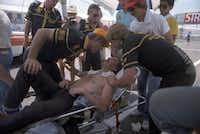 Driver Nigel Mansell is attended to after pushing his car at the end of the 1984 Formula One Grand Prix championship race at Fair Park in Dallas.(Jan Sonnenmair/The Dallas Morning News)
