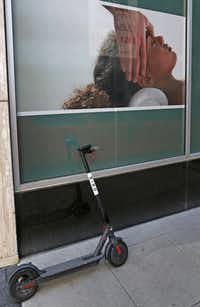 A rental scooter is parked alongside a business poster on Commerce Street in downtown Dallas.(Louis DeLuca/Staff Photographer)