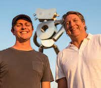 Brandon Oldenburg and Brad Oldham were the artists behind the making of the three-part sculpture series in Deep Ellum. Behind them is the friendly face of <i>The Traveling Man — Walking Tall</i>.(Carly Geraci/Staff Photographer)