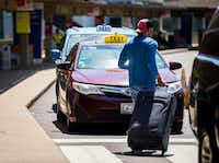 A traveler passes taxi cabs waiting for customers at Terminal A at DFW International Airport.(Ashley Landis/Staff Photographer)