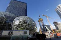 Large spheres take shape in front of an existing Amazon building (back) as new construction continues across the street in Seattle.  (Elaine Thompson/The Associated Press)