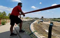 Avid cyclist Ryan Crissey looks out over the partly removed Frisco Superdrome, a cycle-racing track with steep banked curves, in Frisco on Saturday, Aug. 4. Crissey is leading the dismantling of the track, long past its glory days, in hopes of rebuilding it somewhere else.(Tom Fox/Staff Photographer)