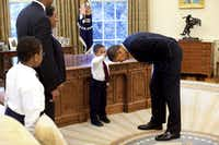 An undated handout photo of Jacob Philadelphia, 5, center, the son of a White House staff member, touches President Barack Obama's hair to see if it feels like his, in the Oval Office of the White House in Washington. (Pete Souza/The New York Times)
