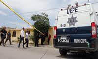 Forensic experts and policemen arrived at the crime scene, after the bodies of 11 people were found inside a house in Ciudad Juarez, Mexico, on Friday.(HERIKA MARTINEZ/AFP/Getty Images)