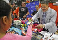 Dallas school board member Jaime Resendez worked in the Bilingual ESL/Dual Language Programs  booth at the Dallas Mayor's Back to School Fair on Friday.  (Louis DeLuca/Staff Photographer)