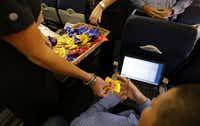 Southwest Airlines Jenni Heikkinen hands out peanuts to passengers on Southwest Airlines Flight 1013 to Denver from Dallas Love Field in 2014.(Vernon Bryant/Staff Photographer)