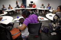 Antranette Canady hugs her 5-yr old grandson, Kwamane Dale during a Women's Independence Network (WIN) support group meeting for former incarcerated women.  The meetings were started by Unlocking DOORS, a Dallas-based nonprofit working to reduce recidivism. The group met for a third time at the Bill J. Priest Institute for Economic Development in S. Dallas, Wednesday, April 22, 2015. DOORS founder, president and CEO Christina Melton Crain said this is one of the only support groups specifically for women after they are released from prison. The Dallas Women's Foundation provided funding for the support group.(Tom Fox/Staff Photographer)