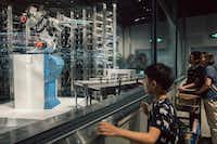 Customers watch robots take cooked food out onto a sort of runway that connects the kitchen to the seating area at the Alibaba-owned Hema grocery store in Shanghai on June 27. (Yuyang Liu/The New York Times)
