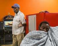 Longtime Dallas resident Elijah Hawkins, left, talks about the news regarding former Dallas Mayor Pro Tem Dwaine Caraway as Tae Shelton, of Dallas, takes a nap at Amigo Wash & Dry in Dallas on Aug. 9, 2018. Hawkins said he was disappointed to hear about Caraway, who will plead guilty to federal corruption charges. He knew him to be approachable and invested in the community.(Carly Geraci/Staff Photographer)