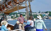 Capt. John Foss (center) explains to passengers how they will climb over the side and down a ladder to the boat they will row to shore in Stonington, Maine.(Robert N. Jenkins/Special Contributor)