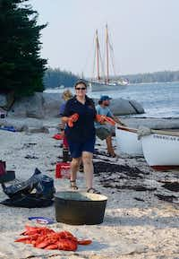 Assistant cook Sarah Collins strolls the beach offering lobsters to eat; there were 40 of them for 26 passengers and crew, plus hot dogs and hamburgers.(Robert N. Jenkins/Special Contributor)