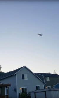 This photo taken from video provided by Courtney Junka shows the stolen Horizon Air turboprop plane flying over Eatonville, Wash., on Friday.(The Associated Press)