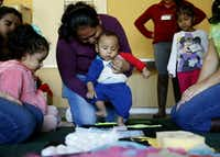 Karen Mena walks her six-month-old son Jose Mena across a cloth with various textures during Juega Conmigo, a weekly parent and child class for children ages 0-3, held at Bachman Lake Branch Library in Dallas on Nov. 20, 2015. Karen Mena uses Vroom, a smartphone app that offers a daily tip about an age-appropriate activity to do with a child. (File 2015/Staff )