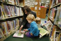 Melodi Smith (top left), of Irving, Texas, reads a book with her daughter, Violet Smith (bottom left), 3, while her other daughter, Lillian Smith, 18 months old, looks through books in the children's section inside the Irving Central Library in Irving Saturday January 31, 2015. (Andy Jacobsohn/Staff Photographer)