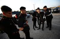 "<p><span style=""font-size: 1em; background-color: transparent;"">Marco Barajas (second from left) gets help from a fellow cadet with his suit. The teens start their night getting ready in a parking lot. </span></p>(Nathan Hunsinger/Staff Photographer)"