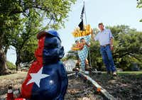 Gary Isett poses with a new addition to his yard — a 6-foot statue of cannibalistic french fries. In front is his Billiken, painted red and blue for the Rangers during baseball season.(Vernon Bryant/Staff Photographer)