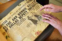 Dallas writer Karen Blumenthal browses a newspaper scrapbook from Sheriff R.A. Smoot Schmid at the J. Erik Jonsson Central Library in downtown Dallas.(Ben Torres/Special Contributor)