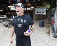 Owner Kerry Bexley prepares to give away a koozie and a bottle of barbecue sauce to a random person waiting in line at Snow's BBQ.(Vernon Bryant/Staff Photographer)