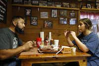 "Pete and Dakota Rodriguez of Houston react after taking their first bite of a rib at Snow's BBQ in Lexington, on Saturday, Aug. 11. The Rodriguezes were first in line when Snow's opened shortly after 5 a.m.(Vernon Bryant/<p><span style=""font-size: 1em; background-color: transparent;"">Staff Photographer</span></p>)"