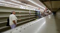 Shoppers pass empty shelves along the bottled water aisle in a Houston grocery store as Hurricane Harvey intensifies in the Gulf of Mexico on Aug. 24, 2017. (David J. Phillip/The Associated Press)